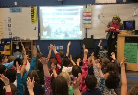 Children at Bell Elementary raise their hands for Paleontology.